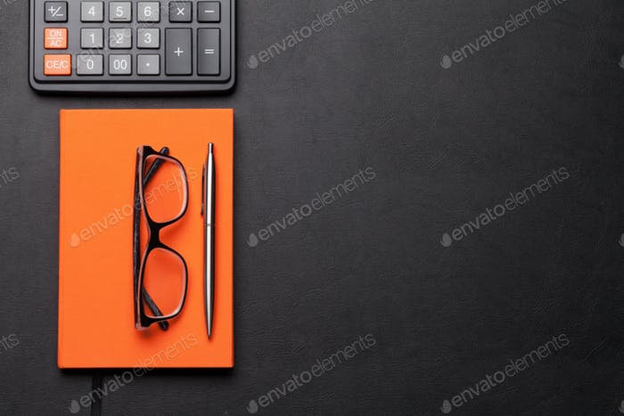 Office workplace table with glasses, supplies and calculator