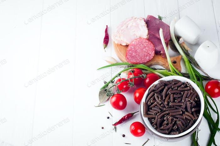 Dry Italian pasta spiraline, red cherry tomatoes, saussage, still life