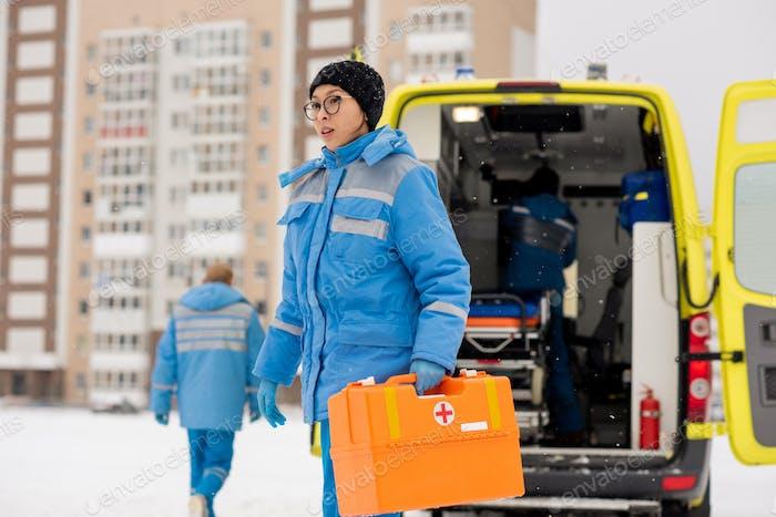 Junge weibliche Sanitäter mit Erste-Hilfe-Kasten während der Eile zu kranken Person im Freien
