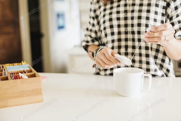 Woman wearing a chequered shirt making a cup of tea.