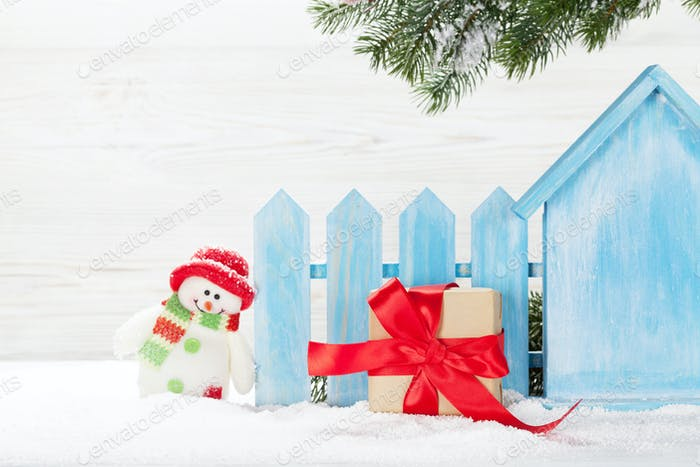 Christmas snowman toy, gift box and fir tree branch