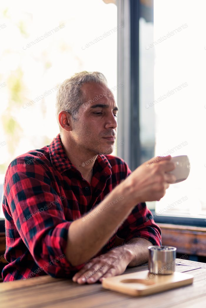 Handsome Persian man relaxing at the coffee shop