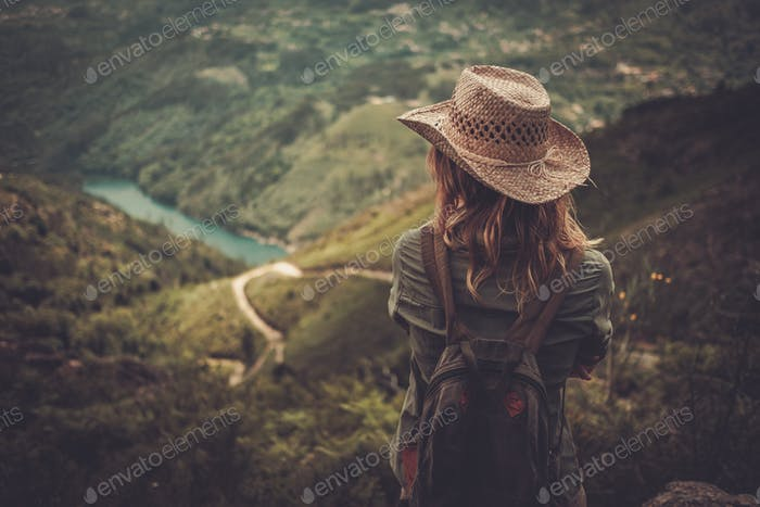 Woman hiker with backpack enjoying amazing valley landscapes on a top of mountain.