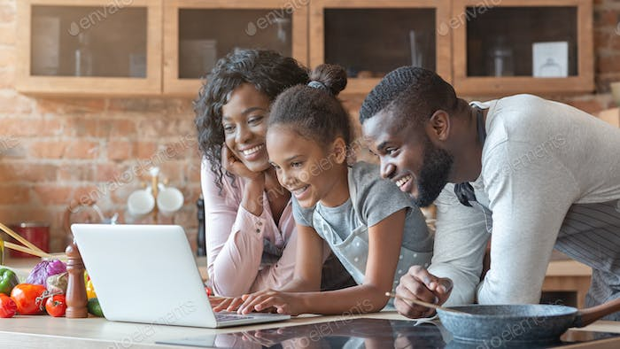 Cheerful family using laptop at kitchen, looking for recipe