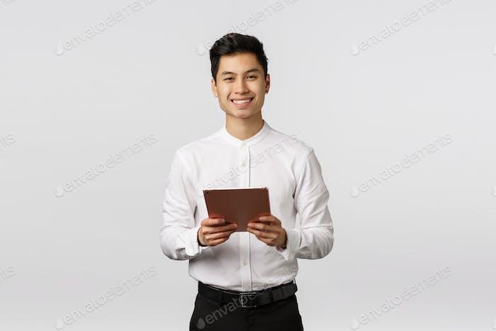 Fröhlich, höflich gut aussehende elegante asiatische Kerl in weißem Hemd, schwarze Hose, hält digitale Tablet und