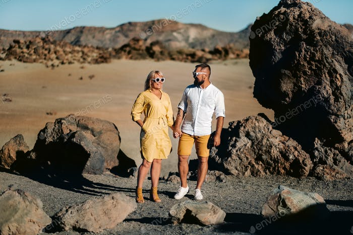 a couple, a woman and a man in the desert crater of the Teide volcano and enjoy the sunset view
