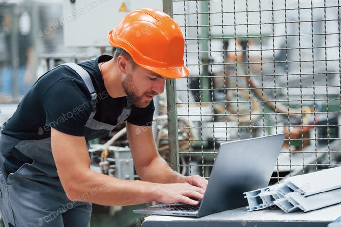 Modern laptop. Industrial worker indoors in factory. Young technician with orange hard hat