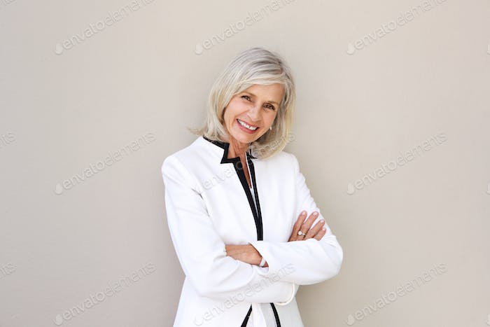 beautiful older woman smiling and standing with arms crossed