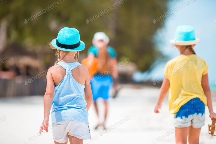 Family of dad and kids walking on white tropical beach on caribbean island