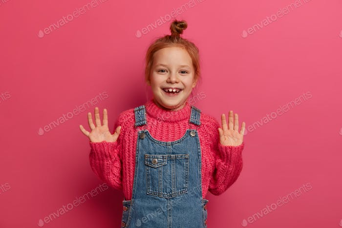 Playful positive girl with ginger hair combed in bun, raises palms and has good mood, poses for fami
