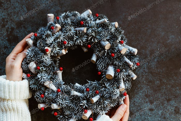 Girl's hands in a winter white sweater hold a Christmas holiday wreath