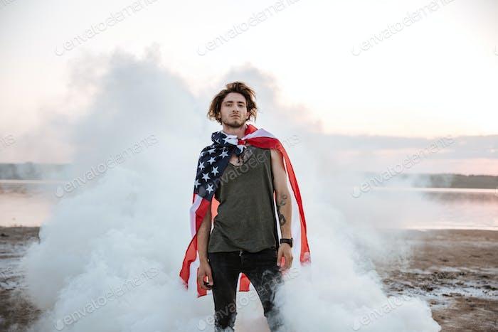 Brutal man wearing usa flag cape posing in white smoke