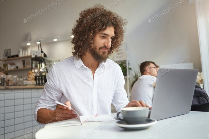 Severe male wearing white shirt checking emails online, using modern laptop, working remotely