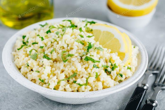 Lemon Herb Couscous in Schüssel auf grauem Hintergrund