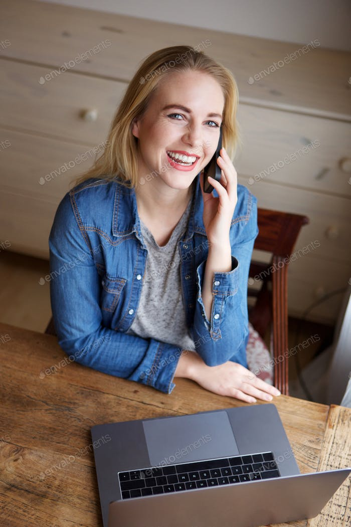 young blond woman with laptop talking on mobile phone