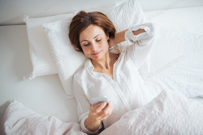 A top view of young woman lying in bed indoors in a bedroom, using smartphone.