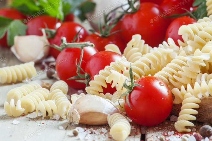 Dry pasta fusilli with tomatoes, selective focus
