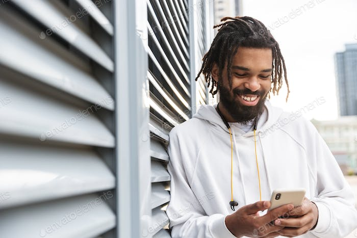 Cheery young man using mobile phone
