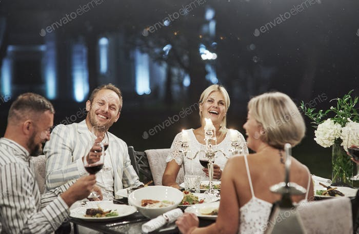 group of adult friends have a rest and conversation in the backyard of the restaurant