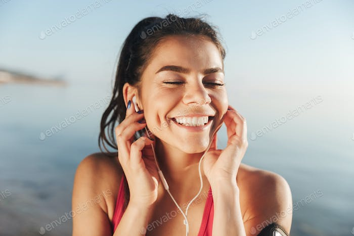 Cheerful sports woman listening music in earphones with closed eyes