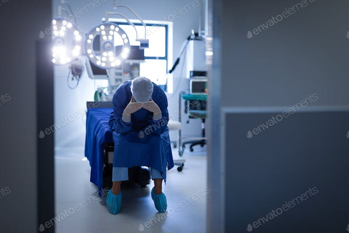 Upset female surgeon sitting on the operation bed in operation room