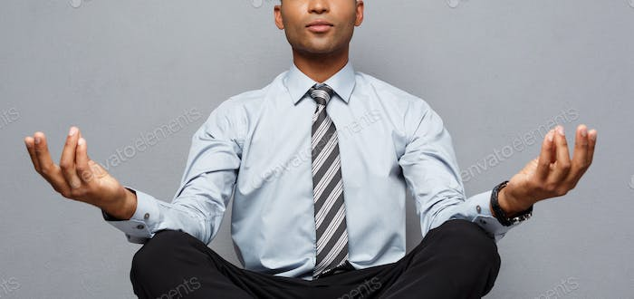 Business Concept - portrait of african american businessman doing meditation and yoga in before