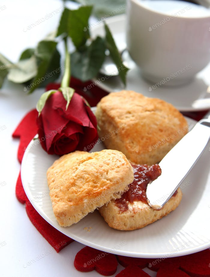 Heart shaped scones with strawberry jam and a cup of tea