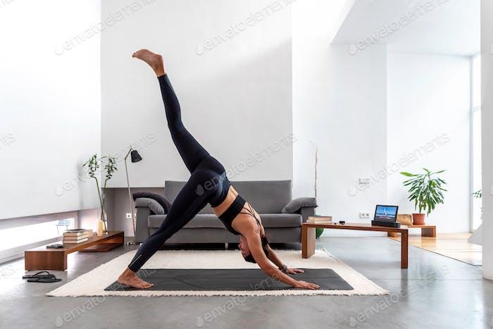 woman doing one leg downward facing dog split at home