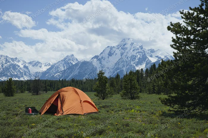 Orange Tent in Field Below Grand Teton Mountains in Wyoming