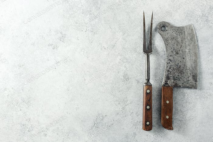 Vintage Meat cleaver and BBQ fork on a empty grey background