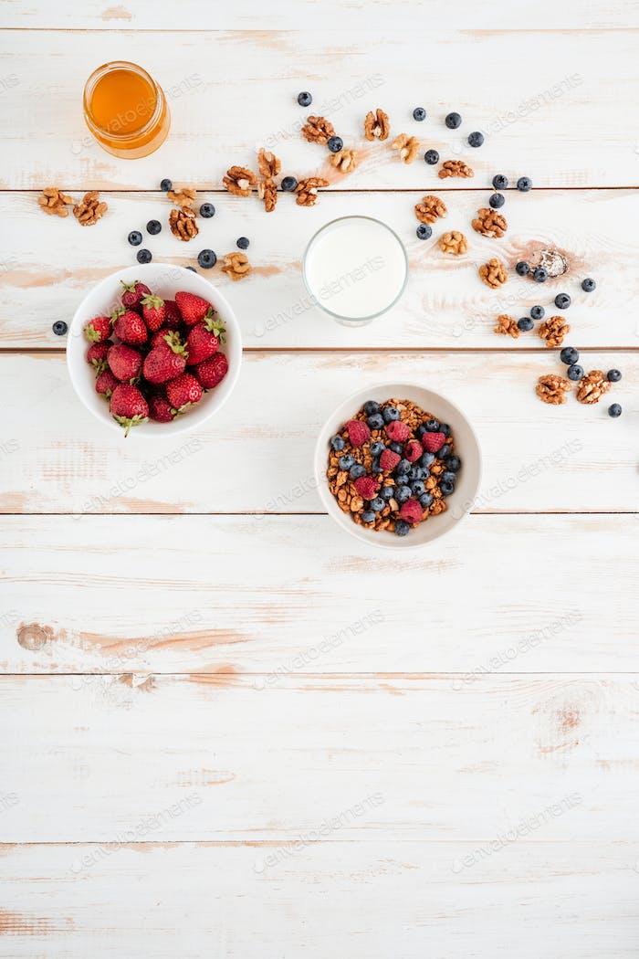 Getreide mit Beeren, Erdbeeren, Walnüssen und Honig