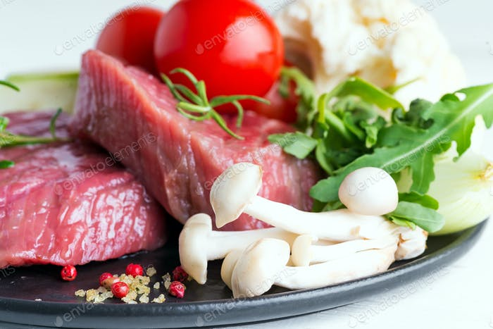 Raw beef steak with fresh vegetables in a pan on a marble background, top view