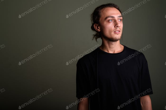 Young handsome man wearing black shirt against colored backgroun