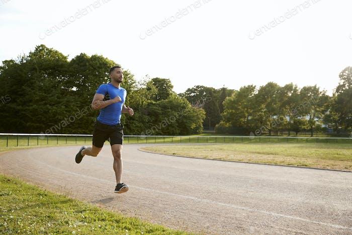 Молодой спортсмен, бегущий на трассе, полная длина