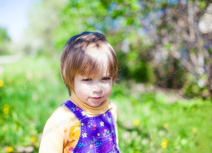 Portrait of small child in jumpsuit outdoors on green nature
