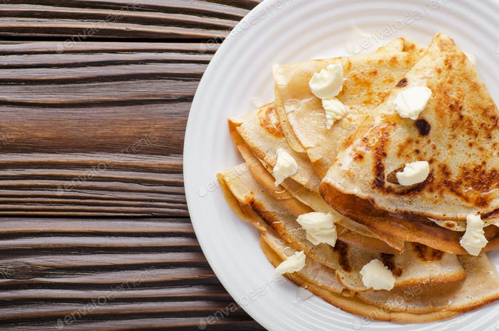 Flat lay of French crepes with butter and honey in ceramic dish