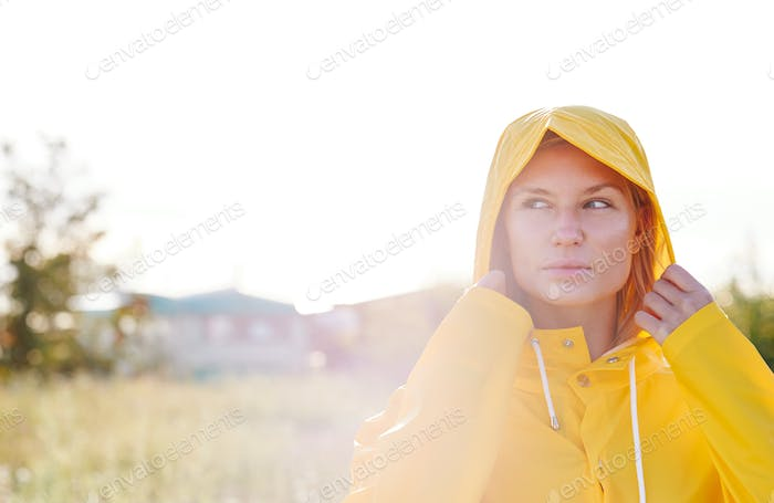 Unhappy Woman Wearing Waterproof Coat At Outdoor Music Festival