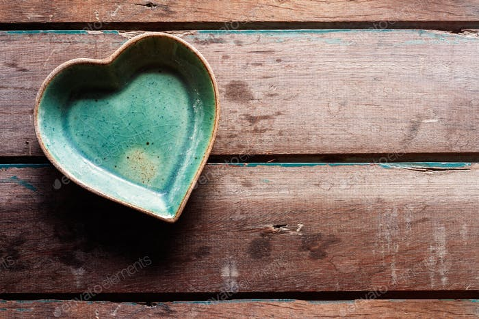 saucer of shaped heart on wood