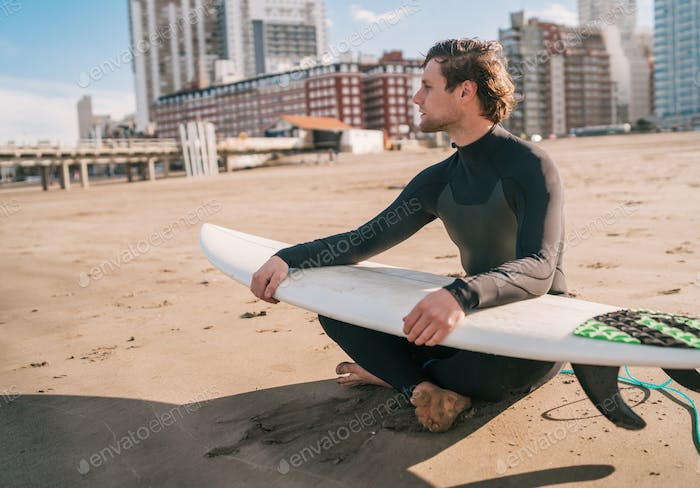 Surfer sitting on sandy beach with surfboard.