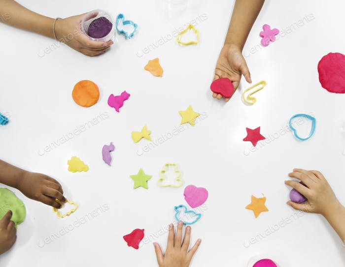 Kids hands with colorful clays on white table