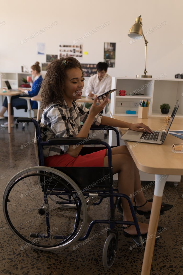young disabled female executive talking on mobile phone at desk in modern office
