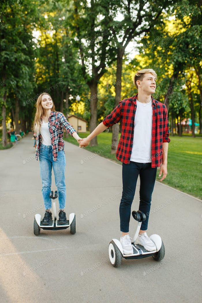 Young couple riding on gyro board in park