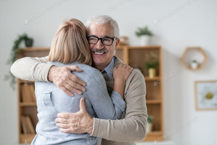 Happy and affectionate senior man giving hug to his blonde young daughter