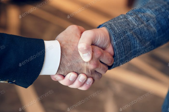 Men shake hands at business meeting