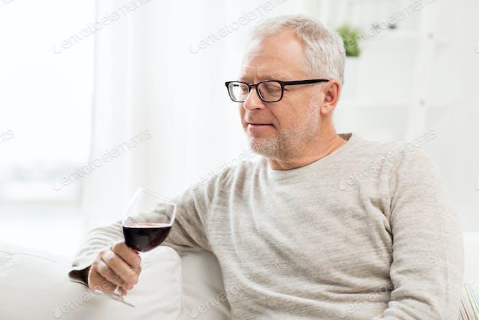 Senior Mann trinken Rotwein aus Glas zu Hause