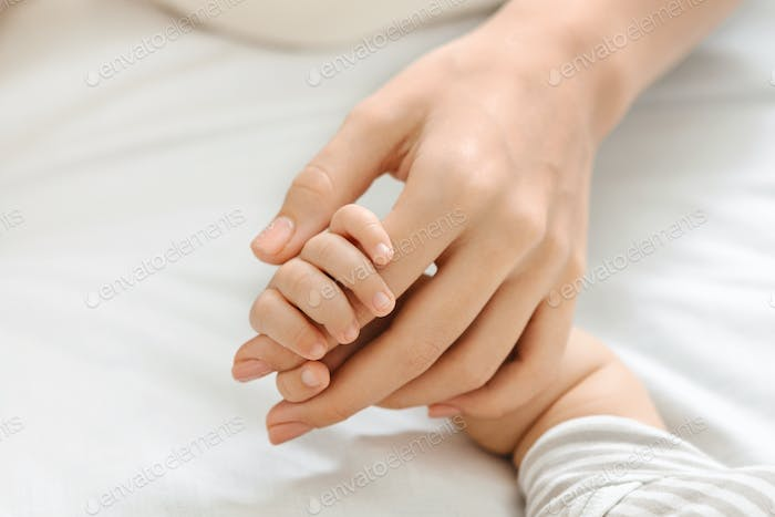 Tiny fingers of newborn baby holding mother's hand, closeup