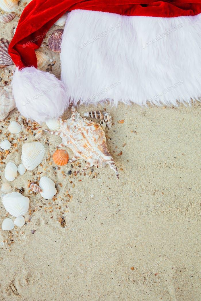 Christmas hat on the beach. Santa the sand near shells.New year vacation.