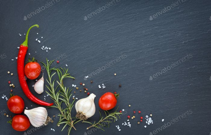 Fresh cherry tomatoes, garlic, salt, pepper and sprigs of rosemary on a black slate board, top view