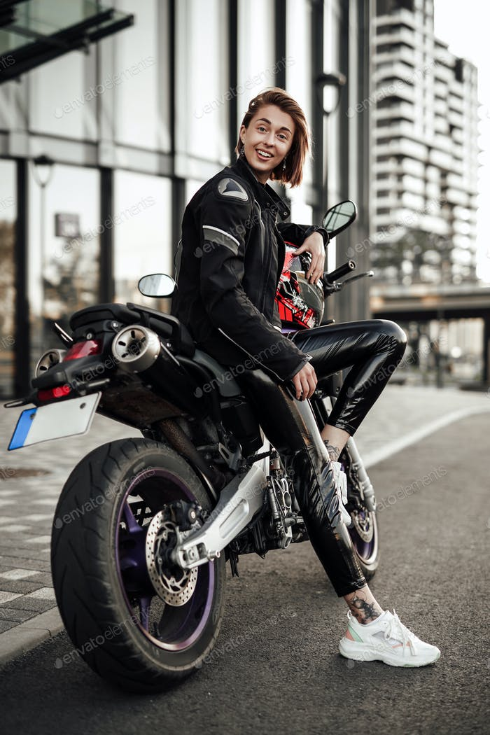 Laughing girl in a black jacket sits on a purple motorbike with a red safety helmet
