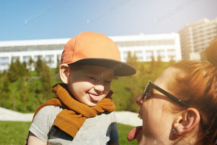 Portrait of adorable two-year old toddler wearing stylish clothes and cap showing tongue to her youn